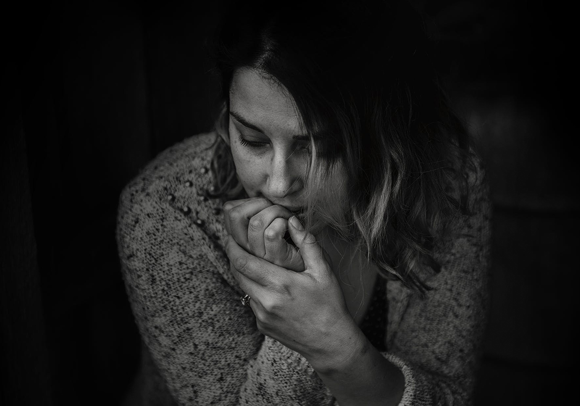 Black and white photo of a nervous woman biting her nails